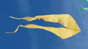 Aquilone giallo con due code in volo contro cielo blu ed il giorno soleggiato archivi video