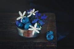 Arándanos azules maduros en una taza del metal con las flores blancas y azules minúsculas de clemátides El estilo rústico Copie e Foto de archivo