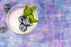 Arándanos frescos en yogur con la menta en la tabla de la lila Imagenes de archivo