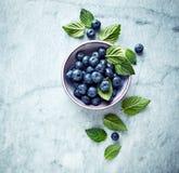 Arándanos maduros frescos con las hojas de menta en un cuenco en fondo de mármol gris Imagen simbólica Concepto para la nutrición imagen de archivo libre de regalías