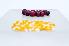 Arándanos frescos al contrario del grupo de píldoras amarillo-blancas en el primero plano Imágenes de archivo libres de regalías