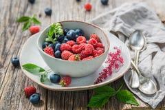 Arándanos y frambuesas dulces en la tabla rústica de madera vieja Foto de archivo