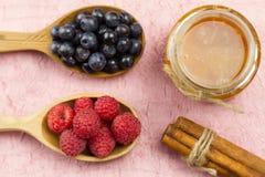 Arándanos y frambuesas en una cuchara de madera y un tarro de miel con canela en una servilleta rosada Alimento vegetariano sano Imágenes de archivo libres de regalías