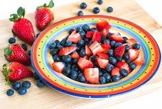 Arándanos y fresas cortados en la placa colorida en el tablero de madera Foto de archivo