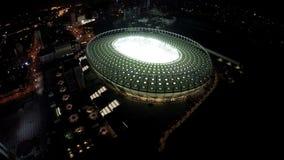 Arène lumineuse du football et lumières urbaines, paysage urbain de nuit, grande ville banque de vidéos