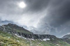 Arêtes de montagne avec le soleil parmi les nuages photographie stock libre de droits