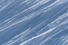Arêtes multiples de neige emballée de vent formant les lignes obliques dans le sunshi Photos stock