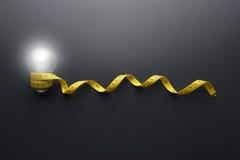 Żarówka i Żółta pomiarowa taśma na popielatym tle Zdjęcia Stock