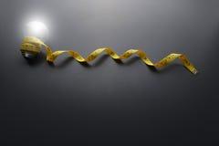 Żarówka i Żółta pomiarowa taśma na popielatym tle Fotografia Royalty Free