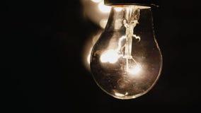 Żarówka zaświecająca jaskrawy przeciw czarnemu tłu zbiory wideo