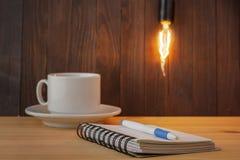 Żarówki pojęcie Pracujący stół Pojęcie nieruchomość nowy pojęcie pomysł Bramkowy położenie jako notatka na notatniku Wygodny stół Zdjęcia Stock