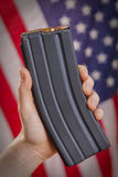 AR-15 magazine with flag. Hand holding a high capacity magazine in front of American flag Royalty Free Stock Photography