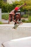 Ar adolescente das capturas ao praticar o skate salte da bacia Fotografia de Stock Royalty Free