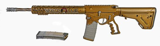 AR15 carbine rifle Moaon AABE Spartan. AR15 rifle painted burnt bronze on a Spartan themed lower and MOAON AABE hand guard, 16` barrel a 30rd mag with a spare stock image
