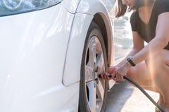 Ar de enchimento em um pneu de carro, inflação do motorista do pneu fotografia de stock