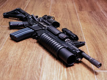 AR15 geweer met granaatlanceerinrichting op de houten vloer stock afbeeldingen