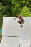 Ar grande das capturas adolescentes que Skateboarding fora da rampa concreta Foto de Stock Royalty Free
