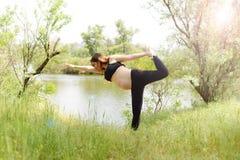 Ar livre bonito grávido da ioga da mulher na grama no dia de verão ensolarado fotos de stock