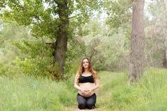 Ar livre bonito grávido da ioga da mulher na grama no dia de verão ensolarado imagem de stock