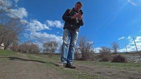 Ar livre de passeio do homem e para encontrar telefone perdido encontrar-se na terra video estoque