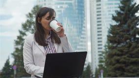 Ar livre de trabalho da jovem mulher e caf? bebendo filme