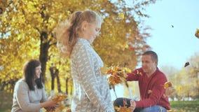 Ar livre feliz da família que joga com as folhas caídas no tempo ensolarado do outono video estoque