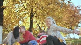 Ar livre feliz da família que joga com as folhas caídas no tempo ensolarado do outono Os pais beijam no fundo vídeos de arquivo