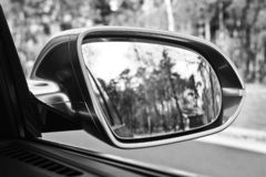 Сar mirror. Forest in rear view mirror close up stock photography