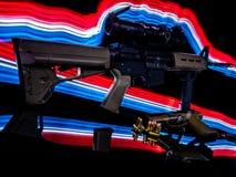 AR-15 och en pistol avteckna sig vid rött, vitt och blått ljus royaltyfri fotografi
