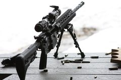 AR-15 rifle with bipod and scope. On a table with spent ammo Royalty Free Stock Image