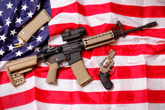 AR Rifle & Pistol on American Flag. An AR Rifle, a Colt pistol and few bullets laying on an American flag.  Shallow depth of field Royalty Free Stock Images