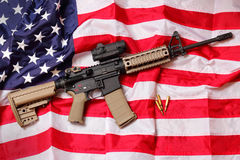 AR Rifle on American Flag. An AR Rifle and few bullets laying on an American flag.  Shallow depth of field Royalty Free Stock Images