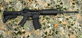 AR-15 rifle. An AR-15 rifle on a generic camouflage background Stock Image