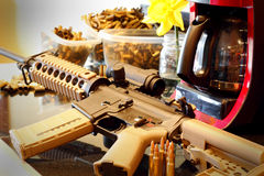 AR Rifle in Home Environment. An AR Rifle laying on a kitchen counter by a coffee pot in a home environment. Bullets in the foreground, empty brass casings in stock image