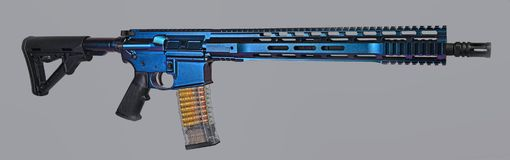 AR15 rifle painted with color changing coating. 16` barrel a clear 30rd mag loaded with visible ammo and ready to go stock photography