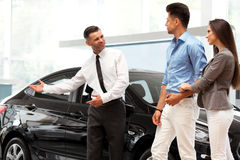 Сar Salesman Invites Customers at Showroom. Royalty Free Stock Photography