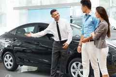 Сar Salesman Invites Customers at Showroom. Stock Images