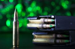 AR-15 shells and a pair of metal magazines. AR-15 ammo and two metal magazines on a green background Royalty Free Stock Image