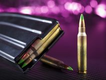 AR-15 ammo with a magazine and purple background. AR-15 steel magazine and ammunition with purple in the background Royalty Free Stock Photo