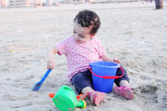 Arab baby girl playing with sand. Happy arab egyptian baby girl playing with sand in local beach in gamasa in egypt Stock Photo