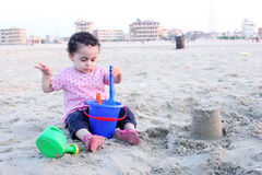 Arab baby girl playing with sand. Happy arab egyptian baby girl playing with sand in local beach in gamasa in egypt Royalty Free Stock Photos