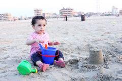 Arab baby girl playing with sand Stock Photo