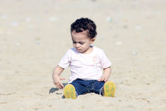Arab baby girl playing with sand. Happy arab egyptian baby girl playing with sand in local beach in gamasa in egypt Royalty Free Stock Images