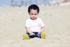 Arab baby girl playing with sand. Happy arab egyptian baby girl playing with sand in local beach in gamasa in egypt Stock Image