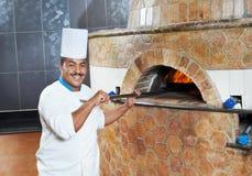 Arab baker chef making Pizza. One arab chef baker in white uniform making pizza at kitchen stock photo