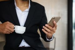 Arab beard businessman use smartphone in coffee time. Arab beard businessman play smartphone and carry coffee cup in cafe. Business man chat, surf social media stock image