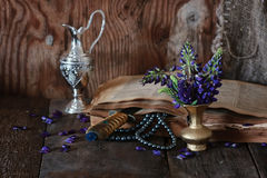 Arab book and flower. Old tattered book on a wooden table textural found an artifact of history Stock Photos