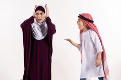 Arab boy is arguing with mother in hijab. stock photography