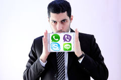 Arab business man with messenger applications logos. Photo of arab business man wearing black suit and holding white tablet withmessenger applications logos on Royalty Free Stock Images