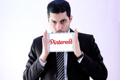 Arab business man with pinterest logo. Photo of arab business man wearing black suit and holding white tablet with pinterest on display Stock Photo